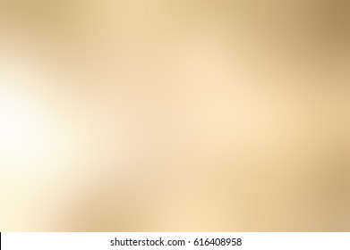 Festive warm silky blurred background. Brass texture. Shining yellow metal abstraction. Gold background. Platinum backdrop.