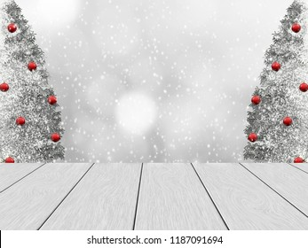 Festive winter design with white wood planks, in the background blurred bokeh, snowy pine and snowfall. The trees decorated with red christmas tree balls. Space for the text.