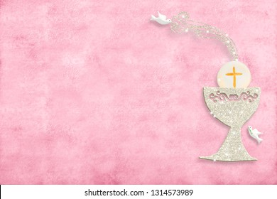 First holy communion invitation card.Silver chalice and doves on pink paper background with copy space to text and photo.