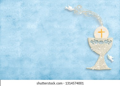 First holy communion invitation card.Silver chalice and doves on blue paper background with copy space to text and photo.