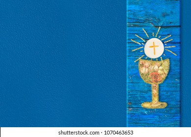 First Holy Communion invitations cards. Gold chalice with flowers  and host on blue background with copy space.