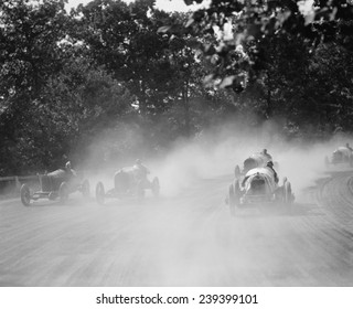 Five racing cars round the track bend in a cloud of dust at the Rockville, MD fair in 1923.