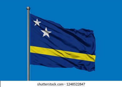 Flag of Curacao waving in the wind against deep blue sky.