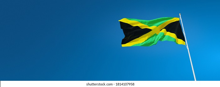 Flag of Jamaica waving in the wind against a wide blue sky. Background with Jamaican national flag isolated. 3D rendering.
