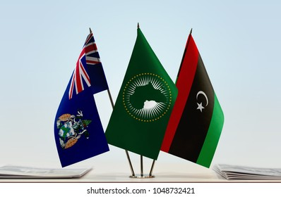 Flags of Ascension Island African Union and Libya. Cloth of flags is 3d rendering, the rest is a photo.