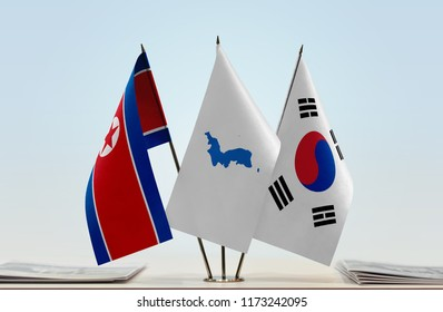Flags of North Korea and South Korea with a Korean Unification flag in the middle. Cloth of flags is 3d rendering, the rest is a photo.