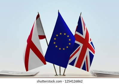 Flags of Northern Ireland (Saint Patrick's Saltire) European Union and Great Britain. Brexit concept. Cloth of flags is 3d rendering, the rest is a photo.