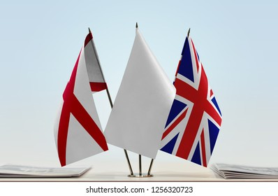 Flags of Northern Ireland (Saint Patrick's Saltire) and United Kingdom with a white flag in the middle. Brexit concept. Cloth of flags is 3d rendering, the rest is a photo.