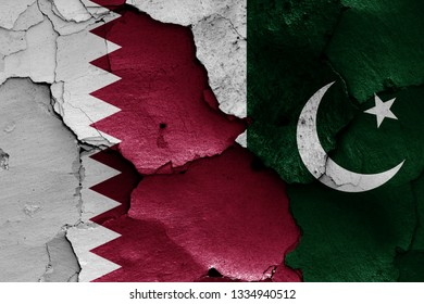 flags of Qatar and Pakistan painted on cracked wall