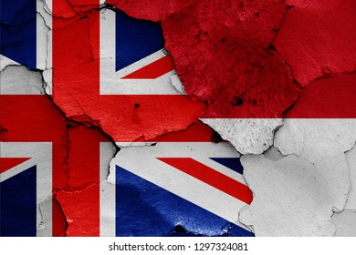 flags of UK and Indonesia painted on cracked wall