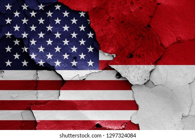flags of USA and Indonesia painted on cracked wall