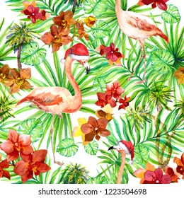 Flamingo in red holiday hats, tropical leaves and exotic flowers. Seamless jungle pattern. Watercolor for Christmas in summer