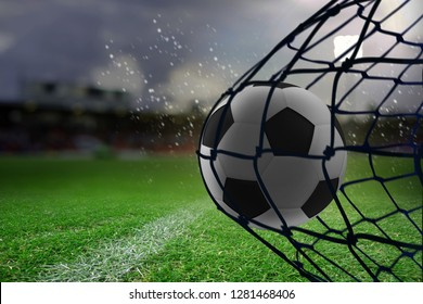 Football hitting the back of the net against close-up of soccer field