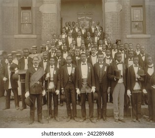 Formally dressed African American men pose with derbies and top hats, and banner labeled Waiters Union in Georgia, ca. 1899. Service occupations such as waiters, porters, and doormen.