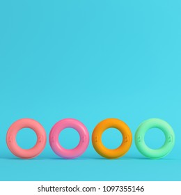 Four colorful inflatable rings on bright blue background in pastel colors. Minimalism concept. 3d render