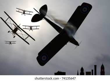 Four double wing vintage world war one biplanes shoot down enemy plane over city. Selective focus on lead biplane and enemy plane going down in flames. Stylized Original illustration