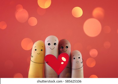 Four fingers decorated as person of different races, holding a big heart shape .