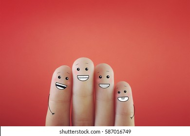 Four fingers decorated as four person with good smile, showing white teeth.