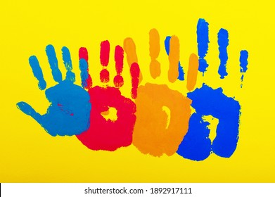 four palms of different colors and sizes on a bright yellow background