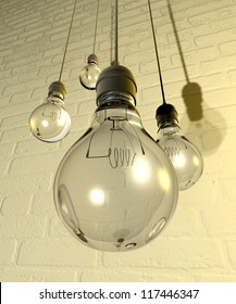 Four regular unlit light bulb fitted into light fittings hanging from chords on a white washed brick wall