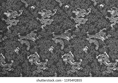 Fragment of grey chinese silk with dragons and flowers