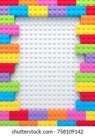 Frame of colorful toy bricks on white construction plate. 3D Rendering.
