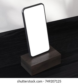 Frameless smartphone with a blank screen is standing on a dark wooden pedestal on a table. Concept of advertising. Three quaters view. 3d rendering mock up