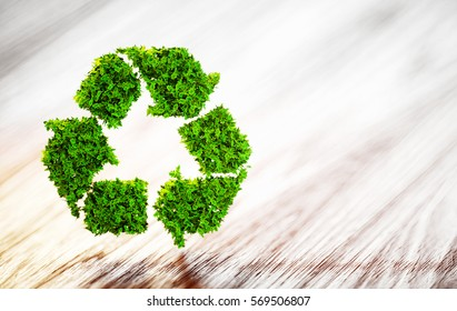 Fresh green leaf recycle symbol on wooden desk with blurred background. 3D illustration.