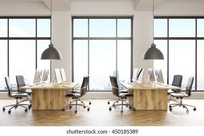 Front view of coworking office interior with computer monitors on wooden desks, parquet flooring, concrete walls and panoramic windows with city view. 3D Rendering