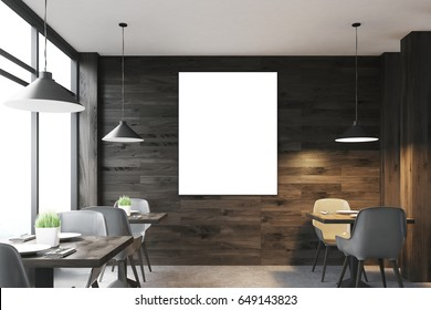 Front view of a dark wooden cafe interior with square tables, white chairs standing along a panoramic window and a framed vertical poster on a wall. 3d rendering, mock up