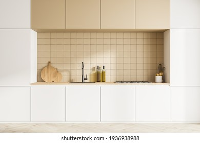 Front view of modern kitchen interior with kitchenware. Parquet floor. White facades and beige ceramic tiles on wall. 3d rendering.