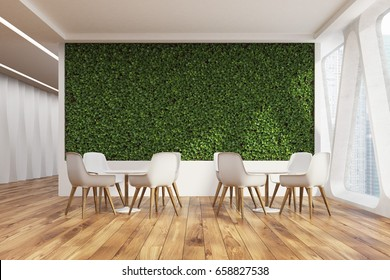 Front view of an office cafe interior with a large grass wall, panoramic windows with triangular frames, white round tables and chairs near them. 3d rendering mock up