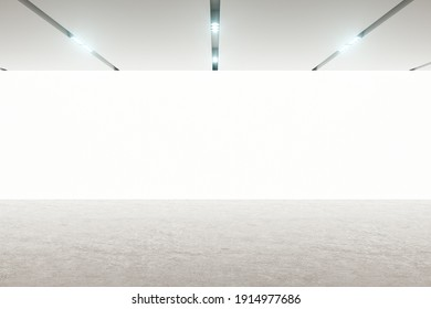 Front view on blank white wall screen in modern empty hall room with concrete floor and led lights on top. Mockup. 3D rendering