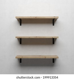 A front view of a regular cleared three wooden shelves with brackets on a white wall