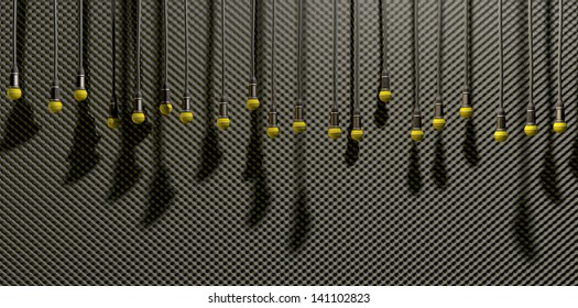 A front view of a row of yellow microphones dangling by cords at various heights on a grey acoustic foam wall background