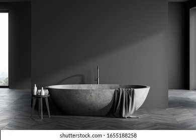 Front view of spacious luxury bathroom interior with grey walls, dark wooden floor, comfortable stone bathtub and chair with towels and beauty products. 3d rendering