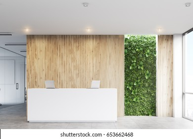 Front view of a white reception desk with two laptops standing on it in front of a wooden office wall. There is a grass wall seen through a wall opening. 3d rendering, mock up