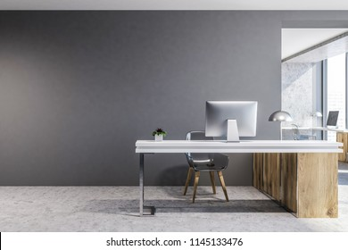 Front view of a wood and gray office workplace with a concrete floor and a computer table. A mock up wall. 3d rendering