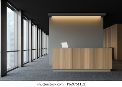 Front view of wooden reception desk with laptop computer on it standing in modern company office with dark gray walls and carpeted floor. 3d rendering