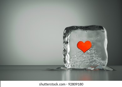 a frozen red heart as a symbol of frozen love, ice cubes with heart, a defrosting process