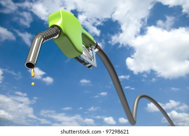 Fuel dripping out of a green fuel nozzle in front of a cloudy sky