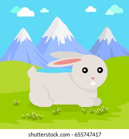 Funny hare sitting on green grass on background of mountain landscape. Gray hare with pink ears. Animal adorable mammal rabbit  character. Natural background. Wildlife character