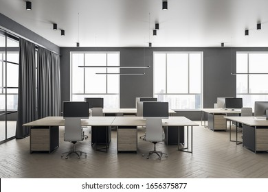 Futuristic grey coworking office interior with equipment and computers on desktop,  furniture and daylight. 3D Rendering