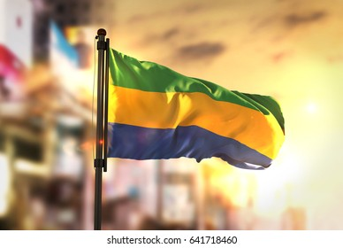 Gabon Flag Against City Blurred Background At Sunrise Backlight 3D Rendering