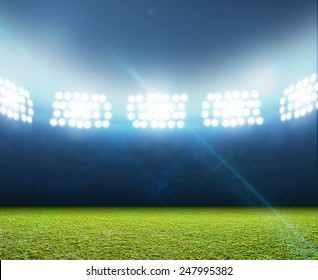 A generic stadium with an unmarked green grass pitch at night under illuminated floodlights