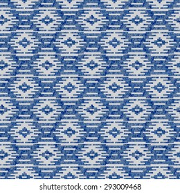 Geometrical abstract seamless pattern from decorative ethnic ornament elements with dark blue watercolor paint texture on a light grey background.
