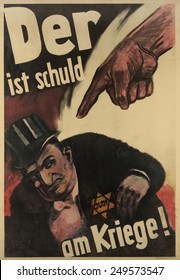 German Anti-Semitic poster. 'Der ist Schuld am Kriege!' translates to 'The war is his fault!'. 1943 WW2 poster depicts a finger pointing accusingly at a man wearing a top hat and with a yellow star.
