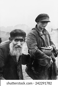 German photograph of two impoverished Jews in Kutno, Poland. 1942.
