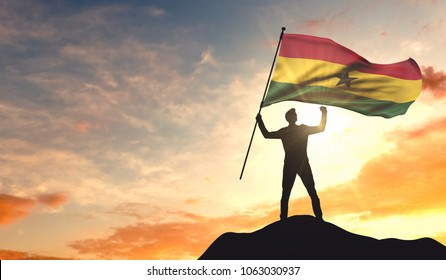 Ghana flag being waved by a man celebrating success at the top of a mountain. 3D Rendering