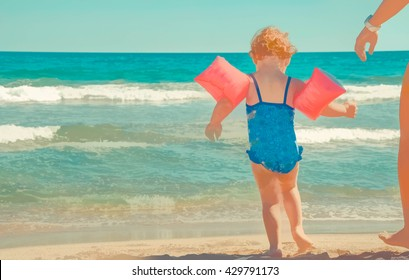 Girl at the shore of the sea with floaties. Her mum is there to give her confident. The image has been simplified to look like a drawing, painting or illustration.
